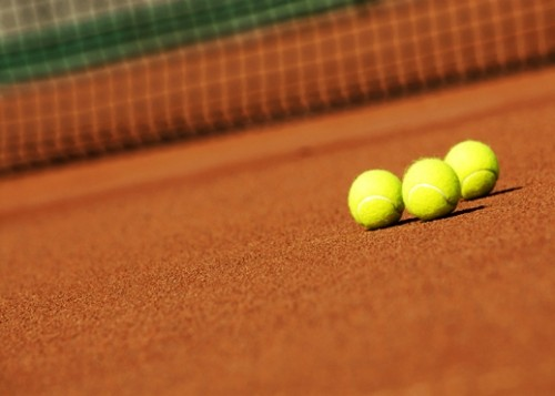 @Glowimages: Three tennis balls on a tennis court